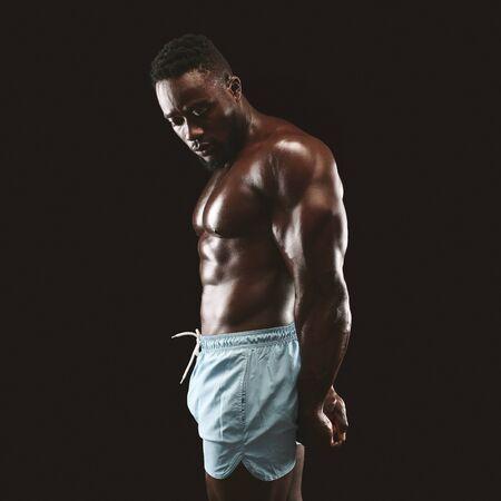 Postura de tríceps lateral realizada por un guapo culturista afroamericano, fondo de estudio negro Foto de archivo