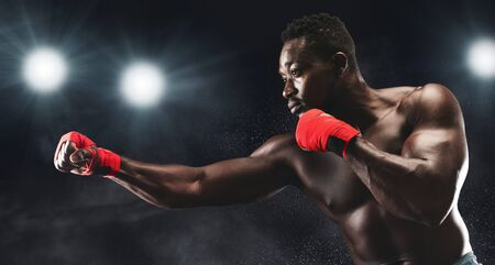Professional african man with red boxing wraps on fighting on boxing arena, stadium lights background, copy space
