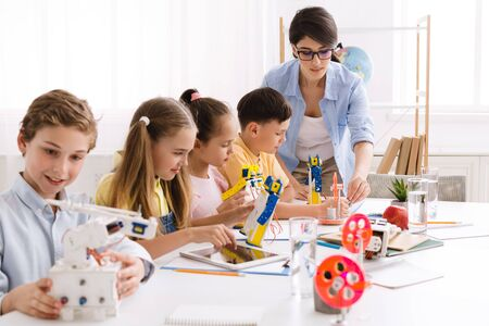 Teacher helping children with diy robots on stem education class, showing how to do