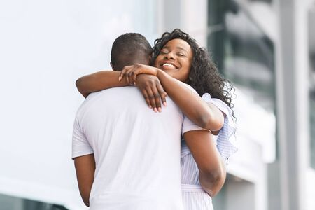 Welcome back. Happy african woman embracing her loving boyfriend, free space Stock fotó