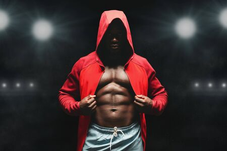 Boxer man workout in boxing ring. Black fighter in hoodie, stadium lights background