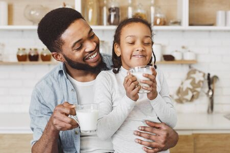 African father encouraging his sweet daughter to drink milk, kitchen background, free space