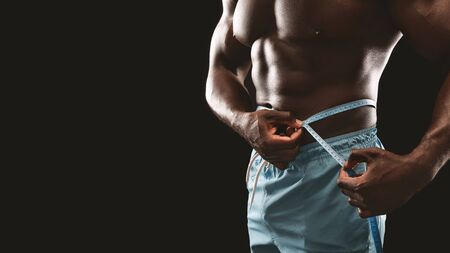 Cropped image of muscular african man measuring his waist. Weightloss, healthy lifestyle, bodycare concept, copy space Stock Photo - 129939160