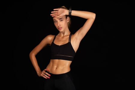 Slim Girl Wiping Sweat From Face After Workout Training Over Black Background. Studio Shot, Empty Space
