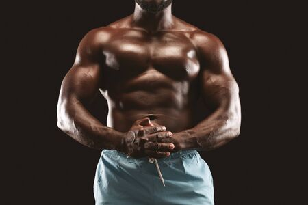 Strong muscular torso of african american male bodybuilder over black studio background, cropped