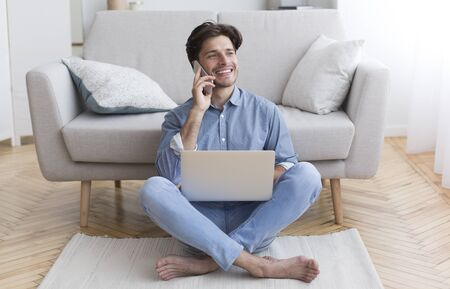 Freelance Career. Guy Talking On Cellphone Using Laptop Sitting On Floor At Home. Free Space For Text Stock Photo