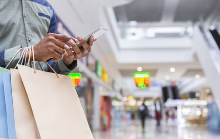 Onherkenbare Afro-Amerikaanse man met mobiele telefoon en aankopen in winkelcentrum, panorama, kopieerruimte Stockfoto