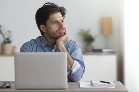 Langweilige Arbeit. Überarbeiteter Kerl, der am Laptop im Büro gelangweilt sitzt Freiraum Standard-Bild