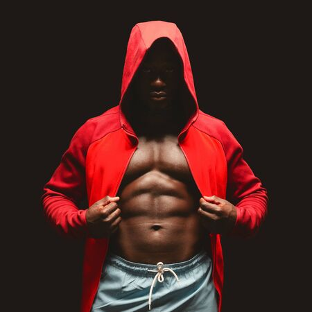 African american muscular fighter in red hoodie over black studio background, close up