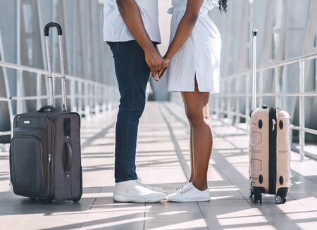 Moment before arrive. Black millennial couple holding hands at airport, standing with luggage