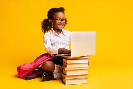 Alegre colegiala afroamericana sentado en el portátil haciendo los deberes sobre fondo amarillo en el estudio.