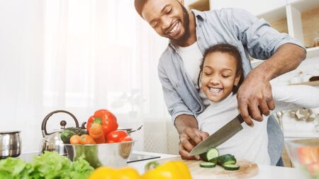 Cooking together. African father and daughter cutting cucumber together, making salad, kitchen interior, copy space Stock Photo