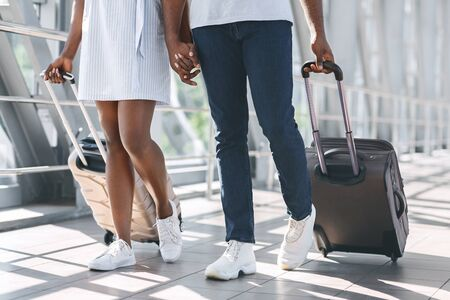 Honeymoon trip. African american newlyweds going with suitcases to flight departure, close-up Stock Photo