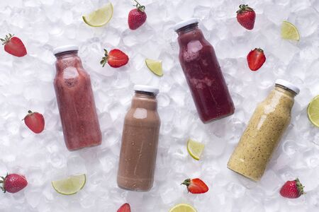 Refreshing detox smoothie drinks with fresh strawberries on ice cubes background