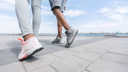 Jogging Concept. Unrecognizable Black Couples Legs Running Along River Embankment In City. Panorama, Cropped, Free Space
