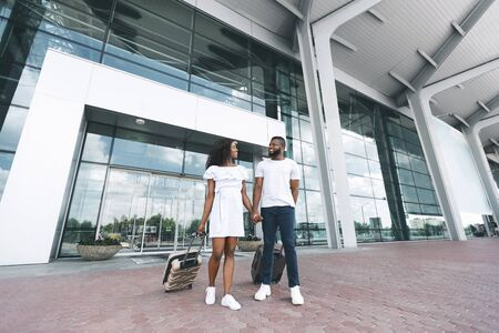 Coming home. African american couple walking out of airport building with luggage, free space