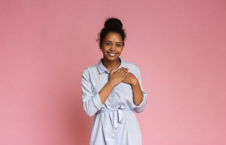 Touched sensitive teenage girl pressing hands to chest being grateful, pink studio background