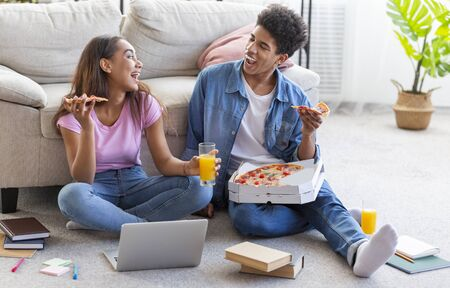 Break in studying. Black teen couple eating pizza and having drinks, sitting on floor with books and laptop at home Stock Photo