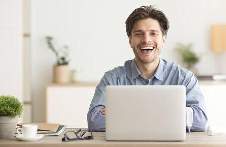 Hombre sentado en la computadora portátil y riendo mirando a la cámara interior. Espacio vacío para texto