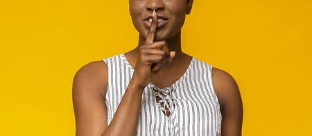 Keep silence. Black young woman showing silence sign, placing finger next to lips, yellow studio background
