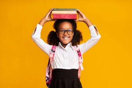 Schattig zwart schoolmeisje met boeken op het hoofd over gele achtergrond. Terug naar schoolconcept, studio-opname