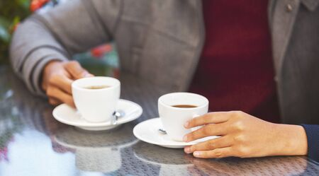 Coffee break concept. Black couple drinking coffee in cafe, close up Stock Photo