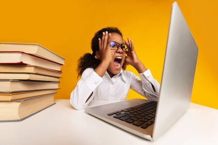 Angry African American Schoolgirl Screaming At Laptop Doing Homework Over Yellow Background In Studio. School Overwork And Stress