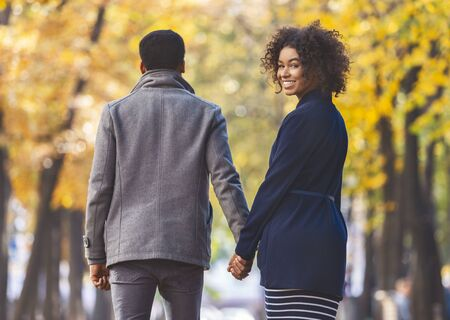 Back view of walking african american young couple over autumn park, girl looking at camera over shoulder