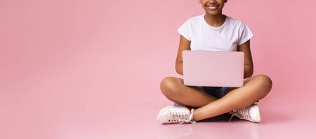 Unrecognizable black teenage girl sitting with laptop on her laps. Pink studio background, panorama