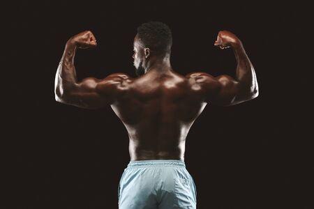 Muskulöses athletisches afrikanisches Bodybuilder-Fitness-Modell, das nach den Übungen posiert, Rückansicht über schwarzem Studiohintergrund Standard-Bild