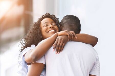 So happy to get home. Cheerful african girl embracing with her lover outdoor