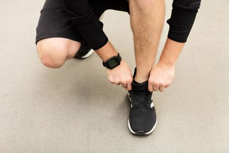 Unrecognizable man fixing shoes before running outdoor, getting ready for workout