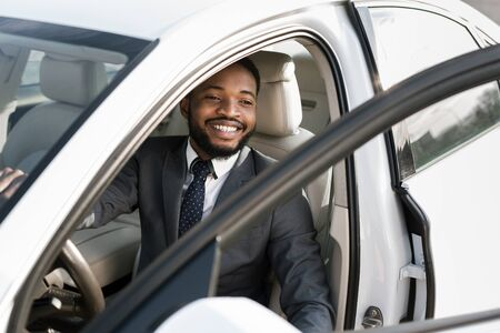 Handsome afro businessman getting out of car, come to office and opening door