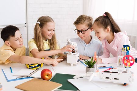 Happy children creating robots at stem class, working together in group Фото со стока