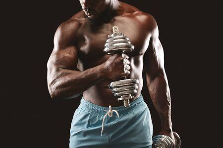 Afrikanischer athletischer männlicher Sportler, der mit Hanteln auf schwarzem Hintergrund trainiert, beschnitten