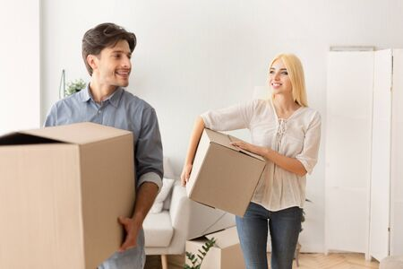 Moving House. Happy Couple Carrying Packed Boxes Entering New Home. Selective Focus Фото со стока