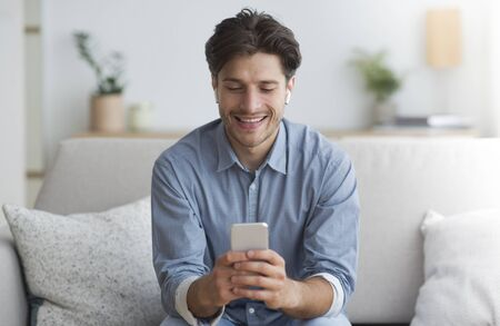 Mobile Games. Cheerful Guy In Wirelss Earphones Playing On Smatphone Sitting On Couch Indoor.