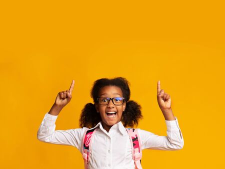 Happy African American School Girl Pointing Fingers Up Showing Something On Yellow Background In Studio. Free Space For Text