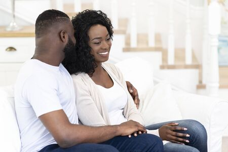 Tender moments. Romantic african american couple sitting on couch at home and embracing.