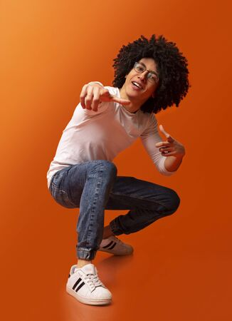 Hey you! Cocky millennial guy pointing at camera, making challenge, squatting on orange studio background