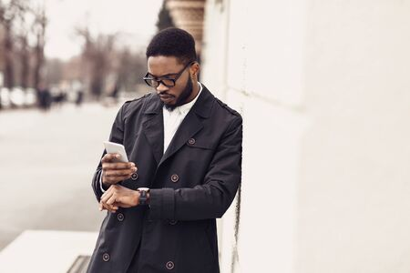 Afro businessman checking time on watches and using phone near office building, free space