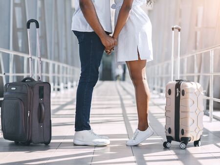 Loving black man and woman holding hands, meeting at airport with luggage, sincere feelings concept