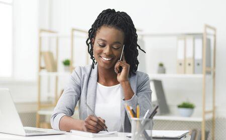 Femme d'affaires noire ayant une conversation téléphonique en prenant des notes dans un bureau moderne. Espace de copie