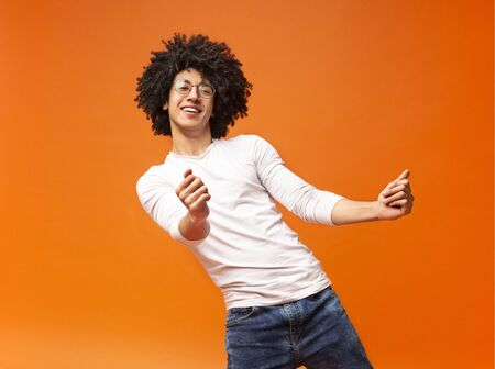Dance with me. Awesome bushy guy dancing club moves on orange background Imagens