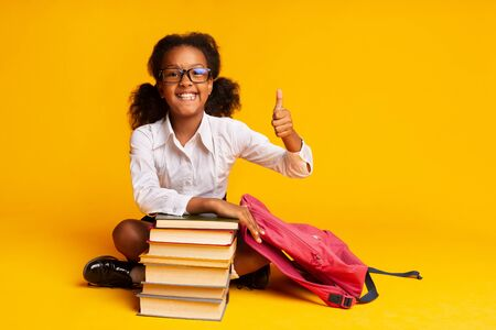 I Like School. Afro Schoolgirl Gesturing Thumbs-Up Sitting At Book Stack In Studio Over Yellow Background. Empty Space