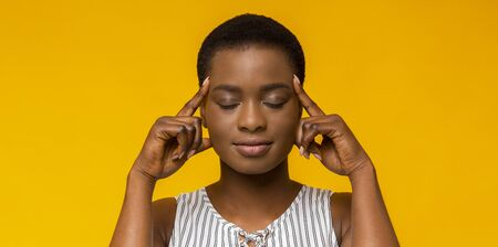 Concentration. Afro girl holding fingers on temples, thinking hard, trying to concentrate, yellow studio background