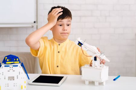 Stem education. Dismayed boy creating robot and made mistake in class Archivio Fotografico