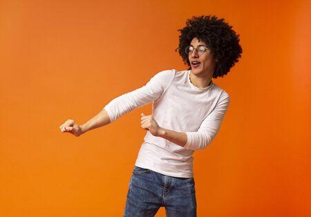 Cheerful bushy black man having fun, dancing on orange studio background Stock fotó