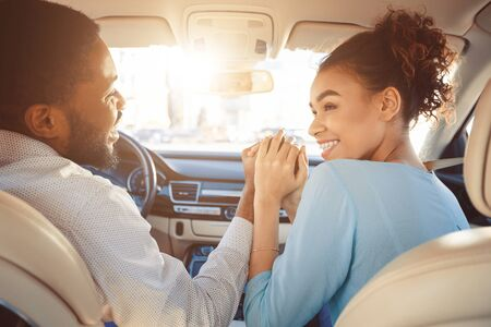 Travel by car. Happy african american couple holding hands, driving in car