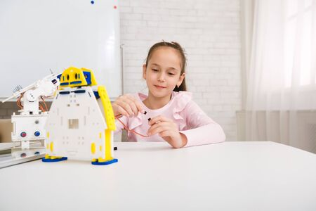Girl programming robot, working with wires and circuits at stem class, free space